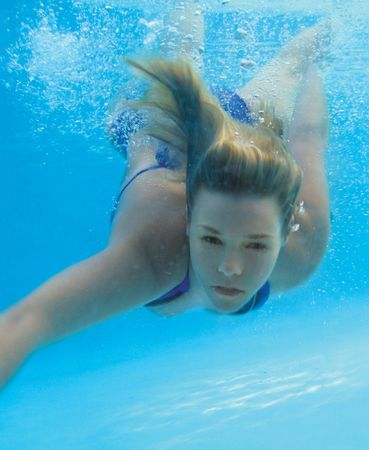 blonde girl diving into pool looking at camera underwater photo