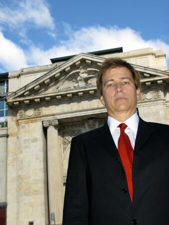 pores: Corporate business looking man in front of stone building Stock Photo