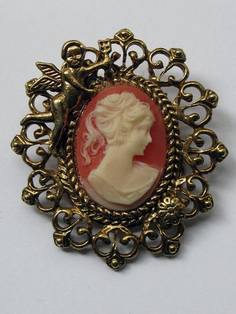 Cameo on clay colored background with cherub golden frame