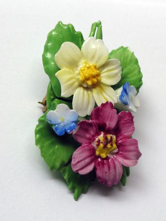 bakelite: Bakelite pendant of yellow, pink and blue flowers on a green leaf