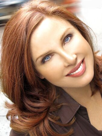 cheeks: Redhead fashion model looking woman smiling in brown shirt outside Stock Photo