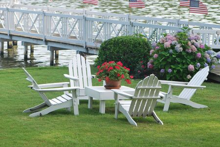 american flags: White Wooden outdoor table setting against dock with American Flags and Red Geraniums Stock Photo