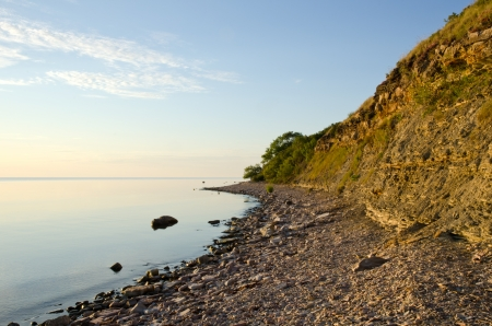 Calm and bright coastline with cliff steep photo