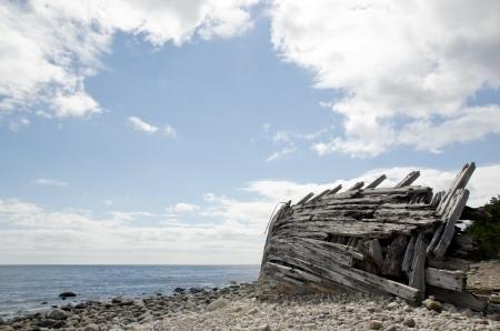 Alte hölzerne Schiffswrack durch eine steinige Küste
