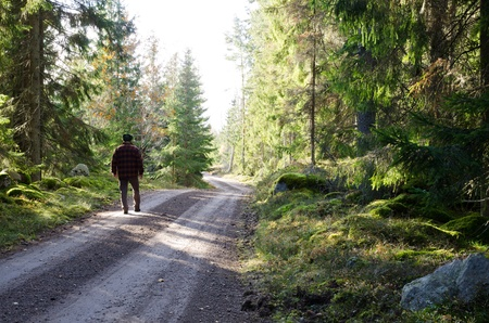 Man walks on a country road in forest photo