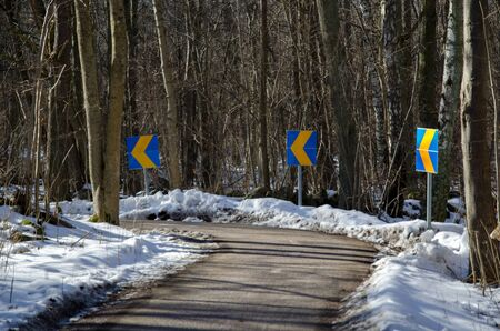 Roadsigns in a curve at a biking trail at wintertime in the forest photo