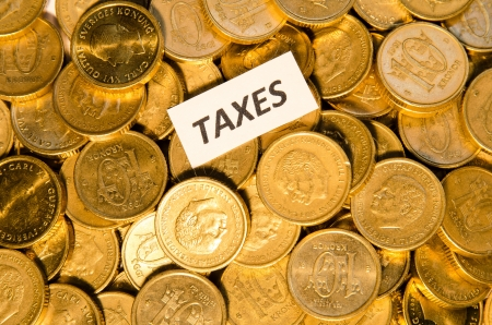 Stack of golden coins with a sign showing Taxes photo
