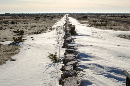 A stonewall with remaining snow cross over the Great Alvar Plain at the island Öland in Sweden photo