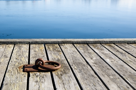A rusty mooring loop at a wooden pier in sunlight Stock Photo - 18943626