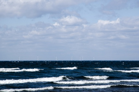 Waves at the coast of Baltic sea with windmills in the horizon  photo