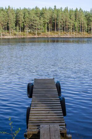 Old empty pier at a calm lake with blue water  From the woodlands in the province Smaland in Sweden  photo