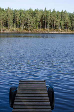 Detail of a pier with old tyres in a calm lake  From the swedish woodlands in the province Smaland  photo