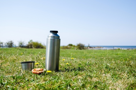 Thermos with bread on a grass field at the coast in springtime  Standard-Bild