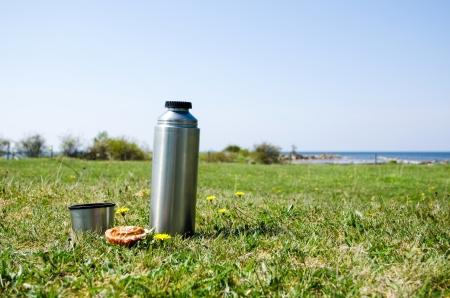 Thermos mit Brot auf einer Wiese an der Küste im Frühling