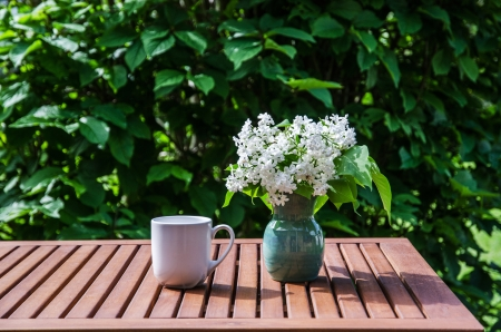White lilacs in a vase and a cup on a table  Stock Photo - 20239491