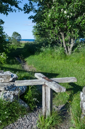 oland: Old wooden turnstile at a pathway to the coast of Baltic sea. From the island Oland in Sweden. Stock Photo