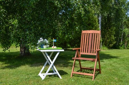 Made table with a swedish flag and a chair in garden at summertime Stock Photo - 20724528