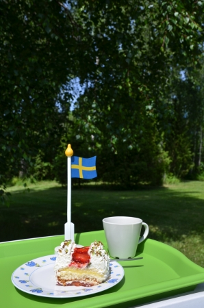Strawberry cake and a cup on a table with a swedish flag in a garden  Stock Photo - 20724534