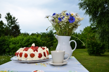 Strawberry cake on a table with summer flowers an a cup outdoors in a garden Stock Photo - 20724554