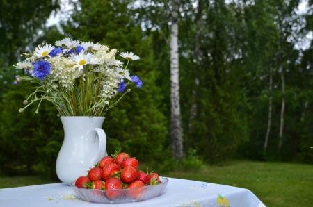 Sommerblumen und Erdbeeren auf einem Tisch im Freien mit grünem Hintergrund Lizenzfreie Bilder