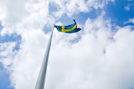 Flag pole wita a swedish flag in the top  photo
