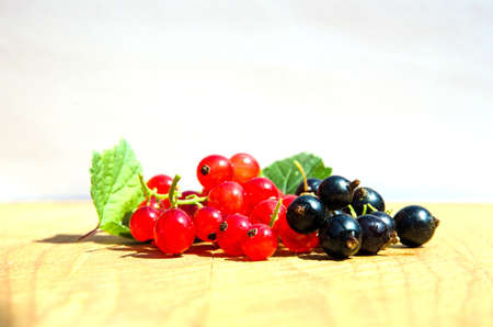 Red and black currants closeup on a wooden table Stock Photo - 21763732