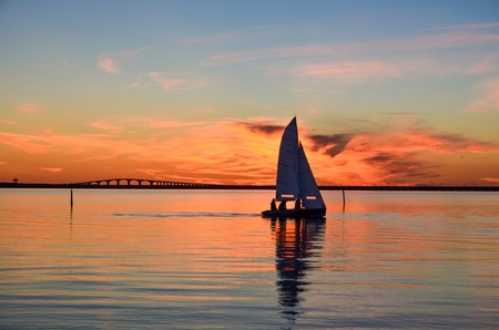 Sailing at sunset in front of the Oland bridge in the Baltic sea, Sweden