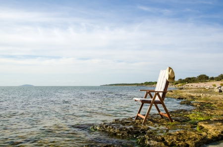 oland: Armchair by the flat rock coast of Baltic sea on the island Oland in Sweden  Stock Photo