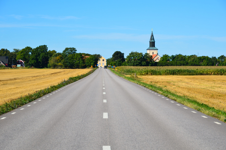 Straight road to the village with church as a landmark Stock Photo
