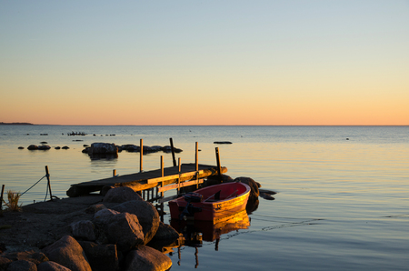 A rowing boat by an old jetty in the last evening sun  From the island Oland in Sweden
