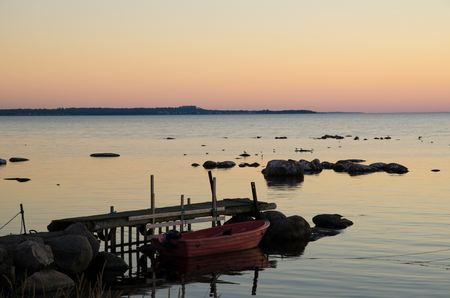 oland: Rowing boat by an old pier at a summer evening  From the island Oland in Sweden