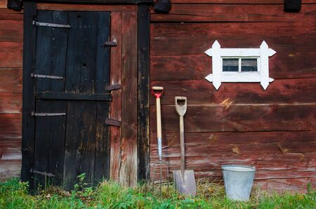 Farmers tools at an old weathered barn wall