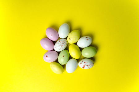 Multi coloured easter eggs confection at yellow background photo