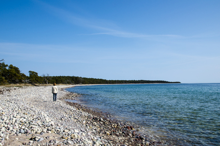 sweden resting: Woman walks at a stony coastline