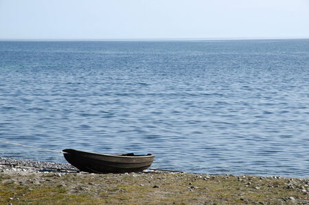 Old black rowing boat at seaside by a calm lake photo