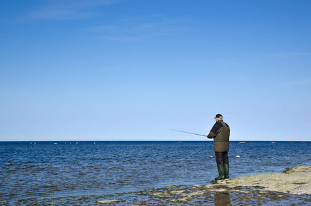 Fisherman at a flat rock coast at blue sky and blue water photo