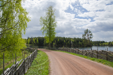 Springtime view from an old gravel road with wooden fence by a small lake photo