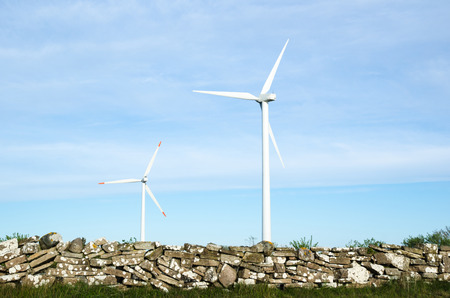 oland: Two wind turbines at blue sky by an old traditional stonewall at the swedish island Oland Stock Photo
