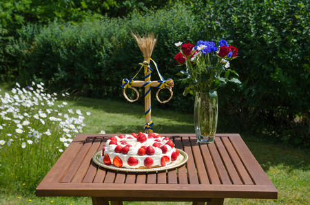 Homemade strawberry cake at a summer decorated table in a garden with daisies Standard-Bild