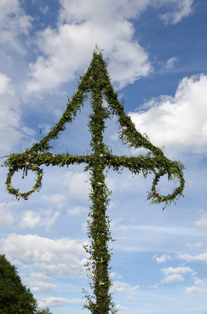 Midsummer pole - swedish tradition - at blue sky with white clouds photo