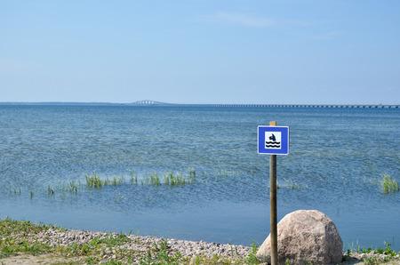 oland: Sign for dog bath beach at the swedish island Oland with the Oland bridge in background Stock Photo
