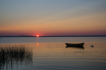 Lone rowboat in calm water at sunset with the Oland Bridge in Sweden as background