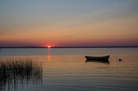 Einsamer Ruderboot in ruhigem Wasser bei Sonnenuntergang mit der Öland-Brücke in Schweden als Hintergrund