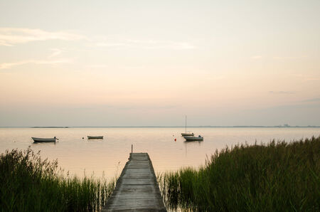 An old wooden jetty with anchored small boats in a calm bay at twilight time photo