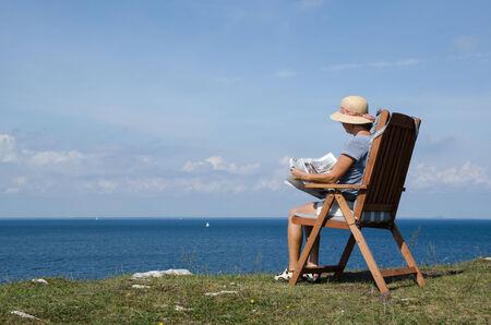 mujer mirando el horizonte: Mujer leyendo el peri�dico en una silla con hermosa vista sobre el mar B�ltico en Suecia