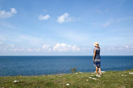 mujer mirando el horizonte: Mujer de pie en verano por la playa mirando el horizonte en el mar B�ltico en Suecia