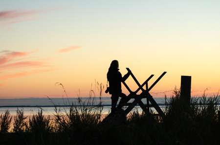 stile: Silhouette of a woman walking over a stile by the coast at twilight time Stock Photo