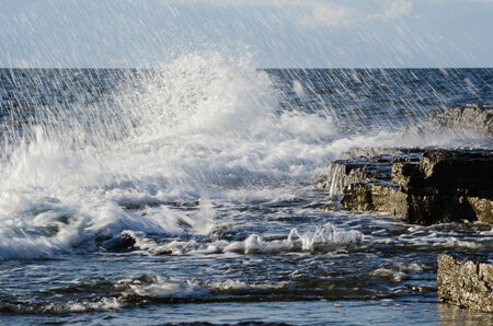 oland: Splashing water at a flat rock coast at the Swedish island Oland in the Baltic Sea Stock Photo
