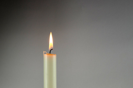 Eine brennende weiße Kerze auf einem grauen Hintergrund