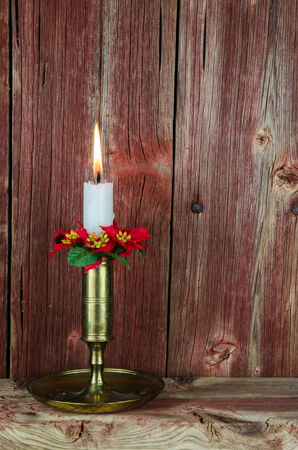 A burning white candle in a decorated candlestick of bronze at an old wooden barn wall photo